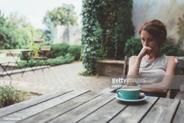 depressed woman drinking coffee at the veranda - relationship difficulties stock pictures, royalty-free photos & images