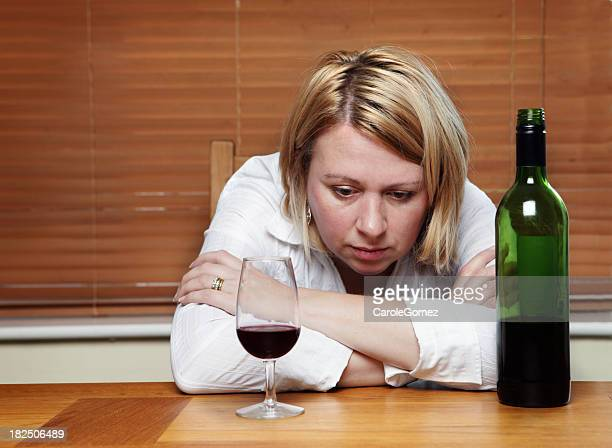 A depressed woman in front of a wine cup and wine bottle