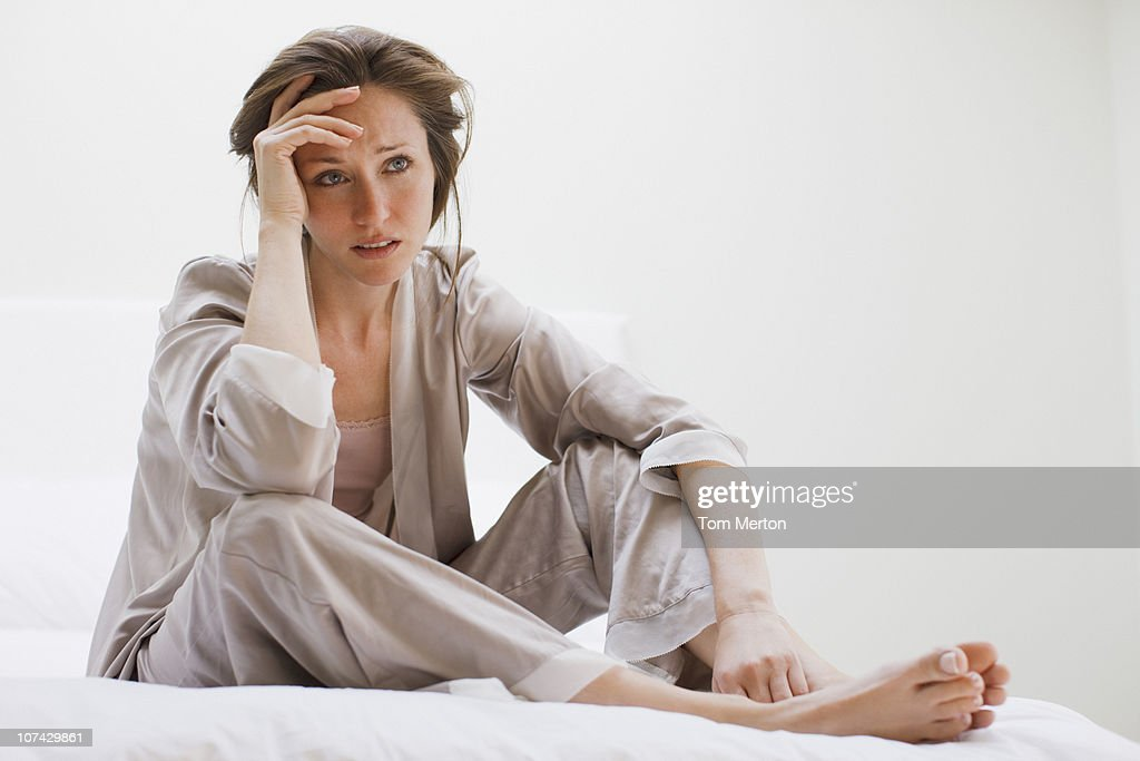 Depressed woman in pajamas sitting in bed : Stock Photo