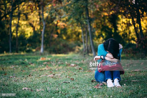 depressed woman in the park - post traumatic stress disorder stock pictures, royalty-free photos & images