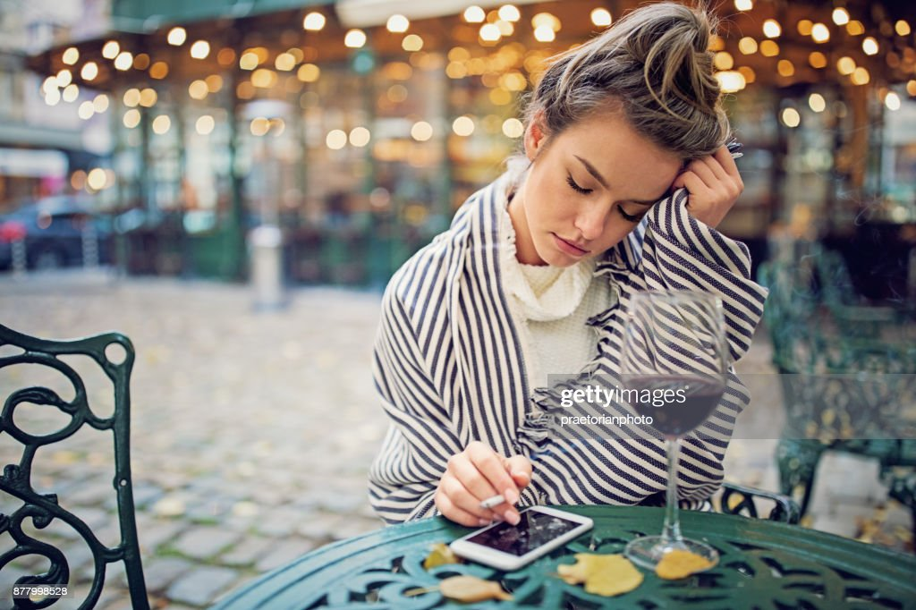 Depressed woman is drinking wine and smoking in a rainy day : Stock Photo
