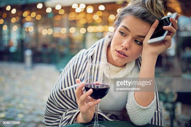 depressed woman is drinking wine, smoking and holding her broken phone in a rainy day - smoking crack stock photos and pictures