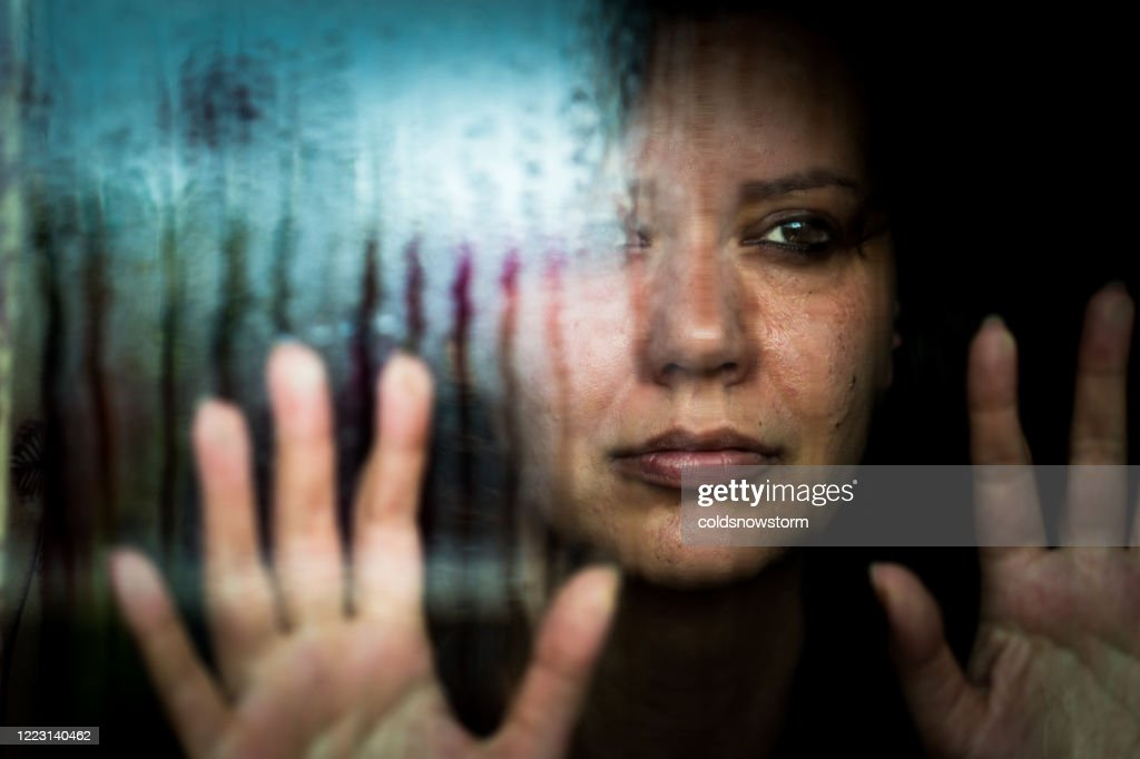 Depressed woman looking out of rainy window : Stock Photo