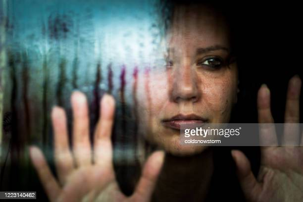depressed woman looking out of rainy window - violence stock pictures, royalty-free photos & images