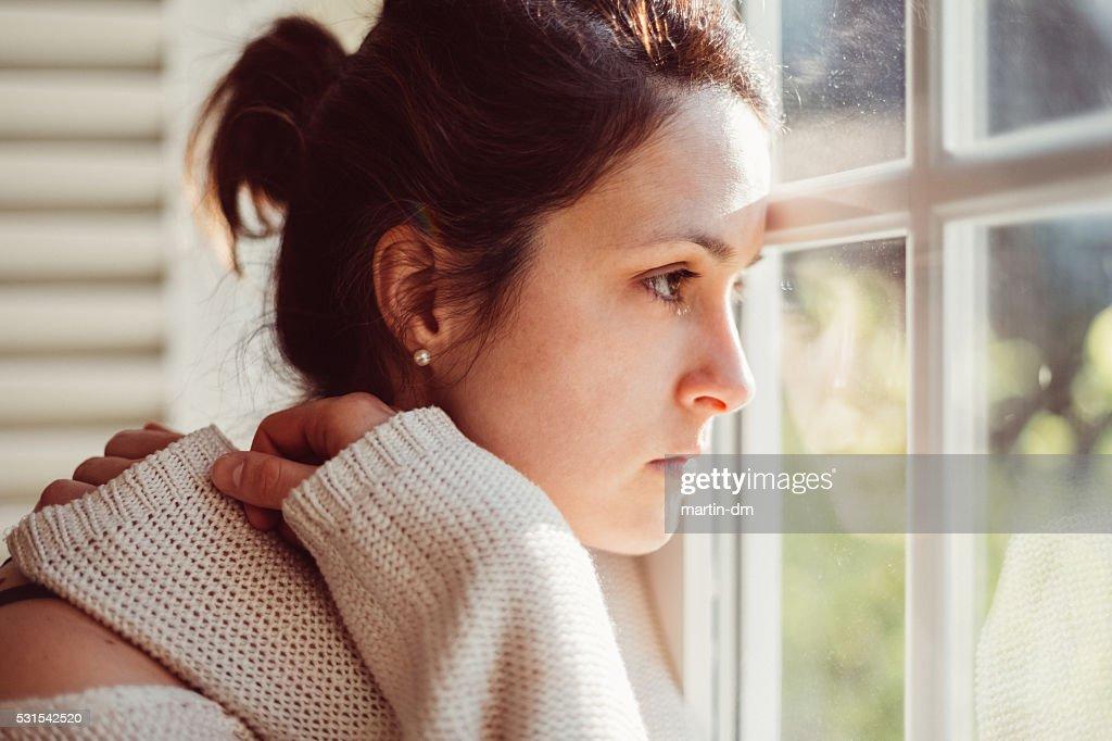Ein deprimierter Frau schaut durch Fenster : Stock-Foto