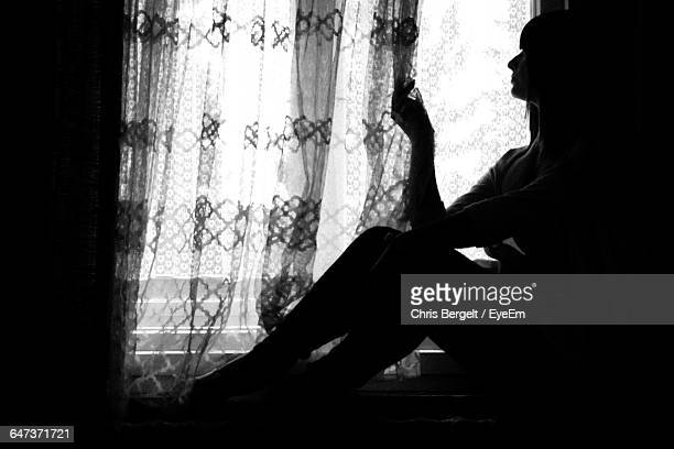 Depressed Woman Sitting By Window At Home