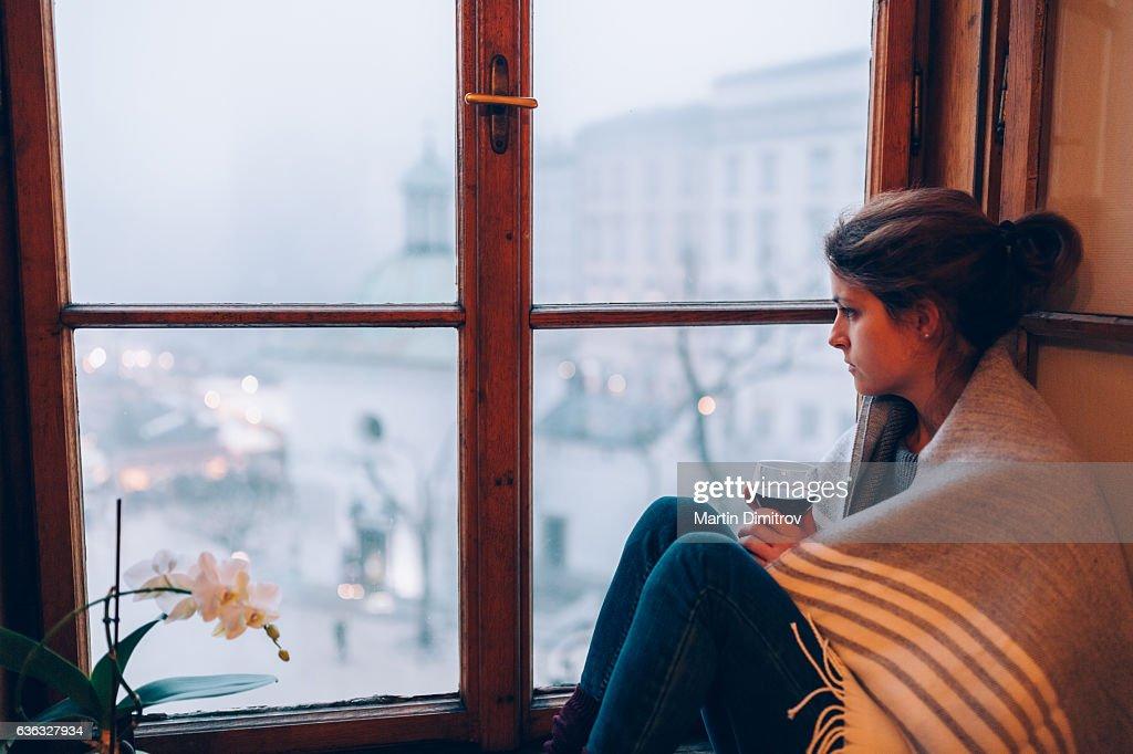 Depressed woman sitting near the window : Stock Photo