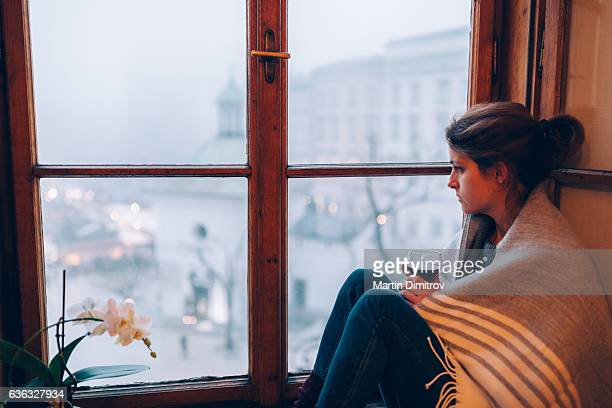 Depressed woman sitting near the window