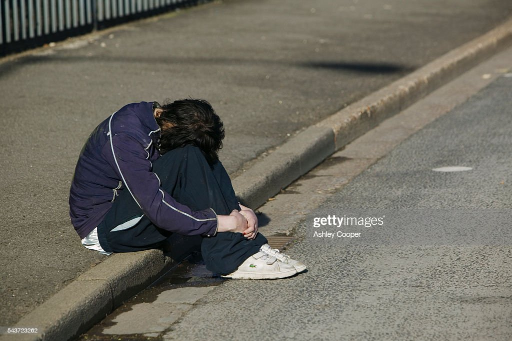Depressed Woman Sitting on Curb : News Photo