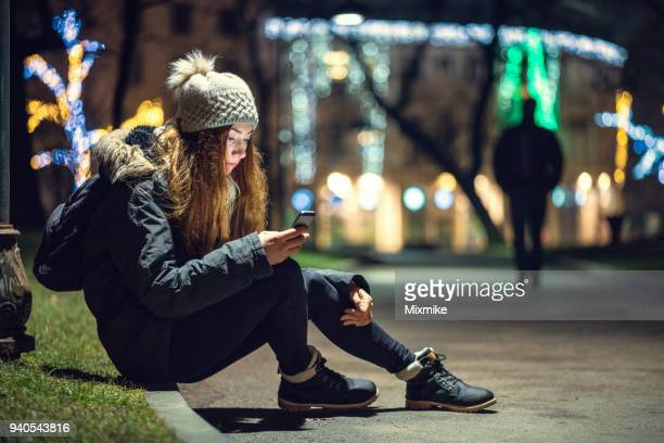 depressed woman sitting under street lamp - vulnerability stock pictures, royalty-free photos & images