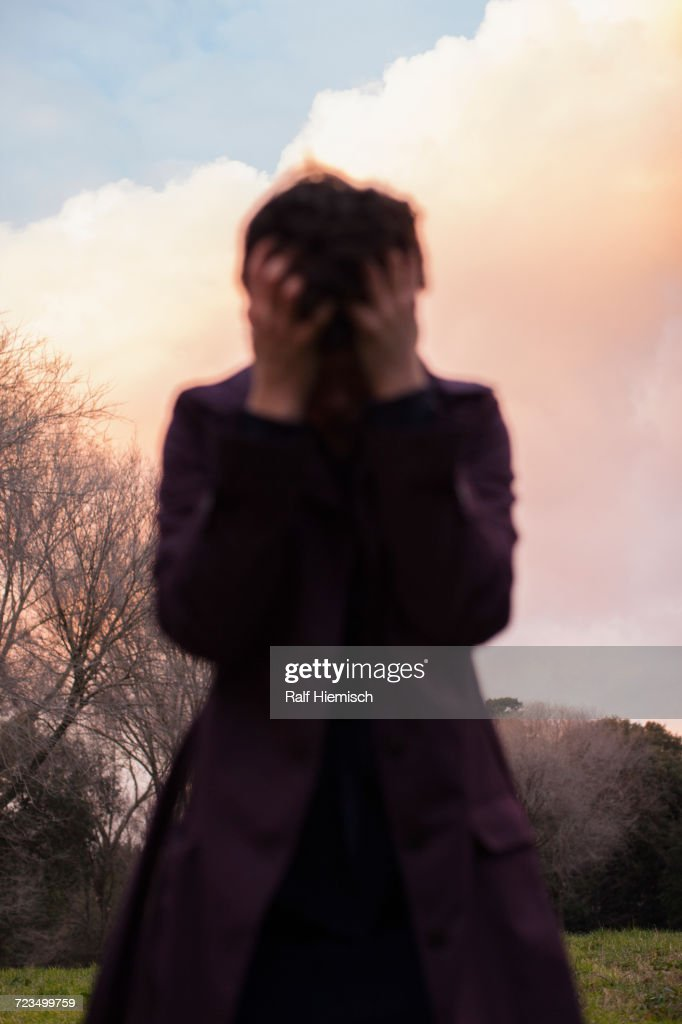 Depressed woman standing against sky during sunset : Stock Photo
