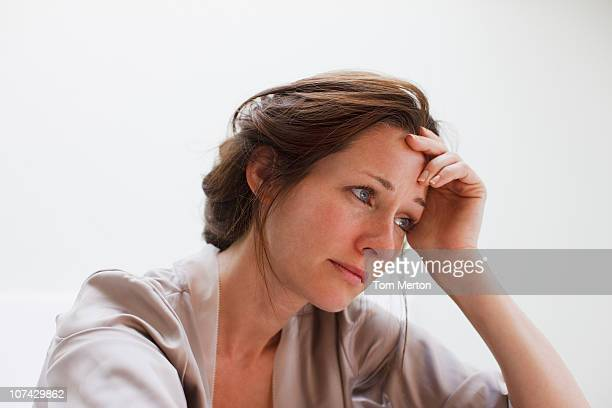 depressed woman with head in hands - ongerust stockfoto's en -beelden