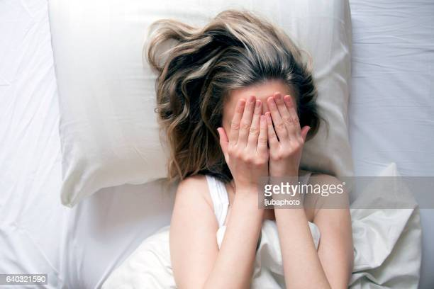Depressed women in bed. Top view of young women