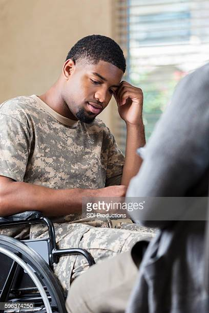 depressed young african american soldier talking to military therapist - injured soldier stock photos and pictures