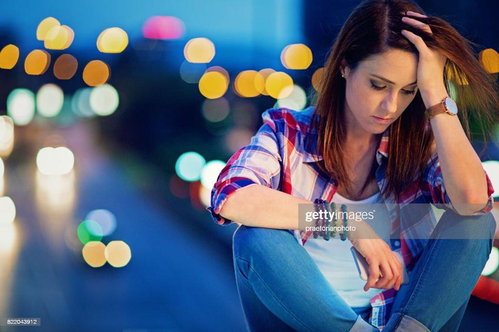 Depressed, young girl is standing sad on the bridge : Stock Photo