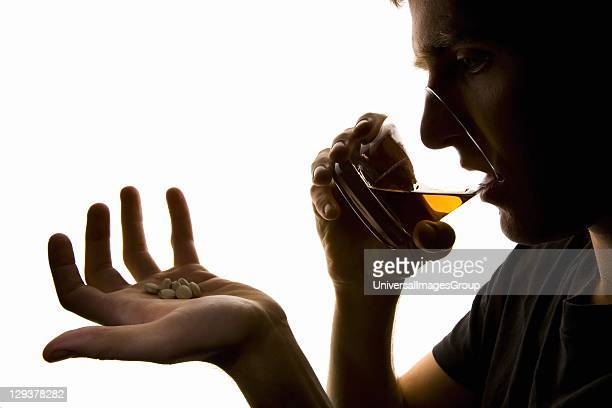 Depressed young man with some sleeping pills and glass of whiskey