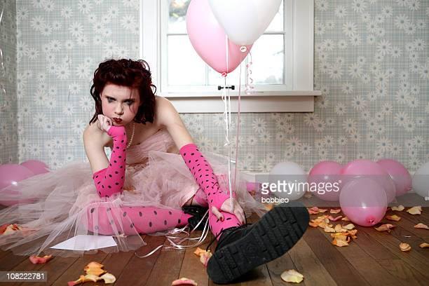 Deprimida joven sentado en el suelo entre papas fritas y globos