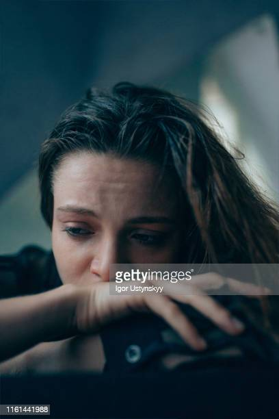 depressed young woman crying - domestic violence stock pictures, royalty-free photos & images