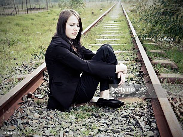 depressed young woman sits on railway tracks - mourning stock pictures, royalty-free photos & images