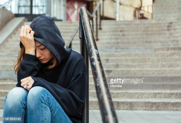 depressed young woman sitting on the street - victim stock pictures, royalty-free photos & images