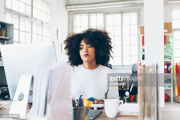 depressed young woman using computer at the office - misnoegd stockfoto's en -beelden