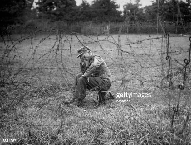 A depressedlooking German soldier in a prisoner of war camp in Normandy