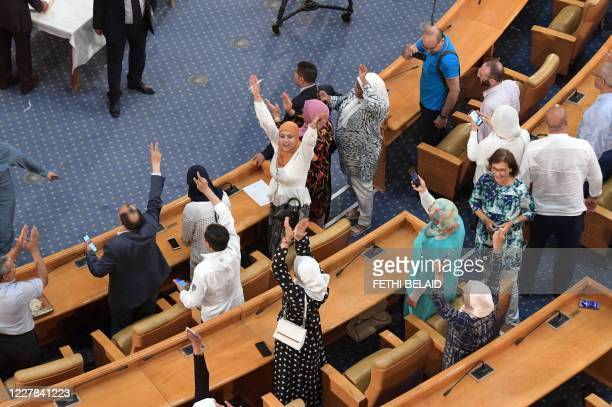 Deputies and members of the Tunisian Islamist Ennahda party rejoice following a plenary session at the parliament in the capital Tunis on July 30,...