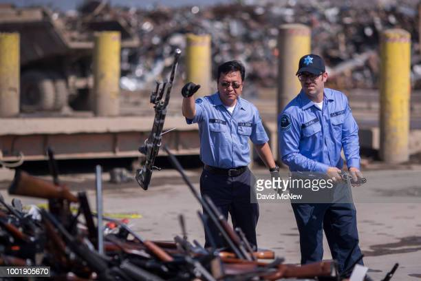 Deputies toss guns onto a pile of approximately 3,500 confiscated weapons to be destroyed at Gerdau Steel Mill under supervision of the Los Angeles...