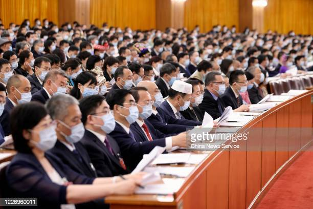 Deputies wearing face masks attend the second plenary meeting of the third session of the 13th National People's Congress at the Great Hall of the...