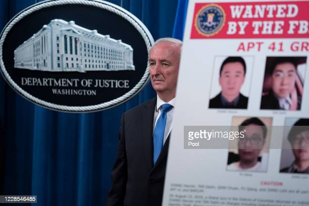Deputy Attorney General Jeffery Rosen listens as FBI Deputy Director David Bowdich speaks to the media about charges and arrests related to a...