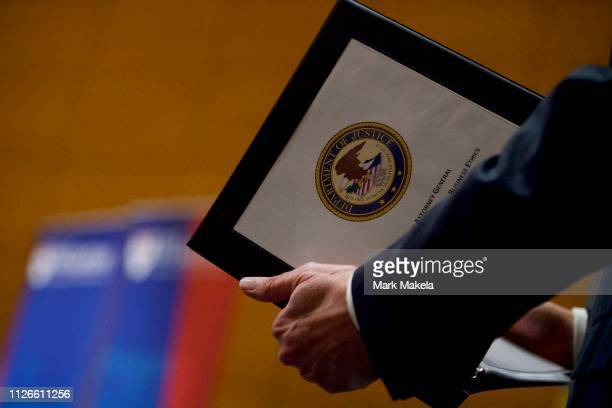 Deputy Attorney General Rod J Rosenstein holds a folder with the Department of Justice emblem before speaking at the Wharton School at the University...