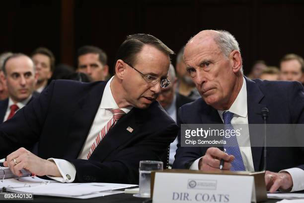 Deputy Attorney General Rod Rosenstein and Director of National Intelligence Daniel Coats talk while testifiying before the Senate Intelligence...