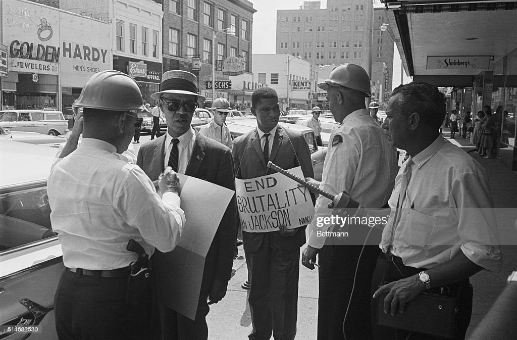 Deputy Chief J.L. Ray (r) arrests Roy Wilkins (l), Executive Secretary of the NAACP, and Medgar Evers, (c) NAACP field secretary who are picketing outside of a Woolworth's department store in Jackson, Mississippi.
