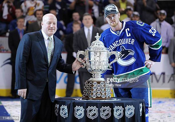 Deputy Commissioner Bill Daly and Captain Henrik Sedin of the Vancouver Canucks pose with the Clarence Campbell Bowl after the Vancouver Canucks...