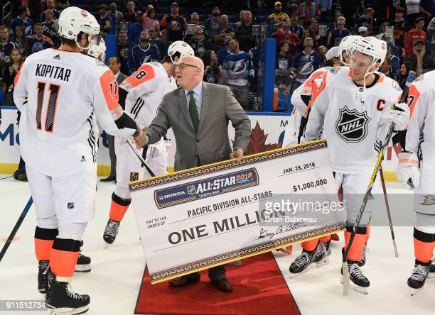 Deputy Commissioner Bill Daly presents the Pacific Division AllStars the one million dollar check and shakes the hand of Anze Kopitar of the Los...