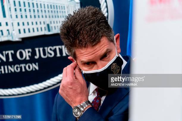 Deputy Director David Bowdich takes off his facemask as he prepares to speak at a news conference at the Department of Justice, October 19 in...