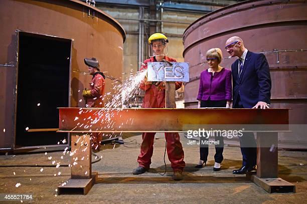 Deputy First Minister Nicola Sturgeon and Cabinet Secretary for Finance John Swinney look on as 19 year old apprentice fabricator Craig McKee angle...