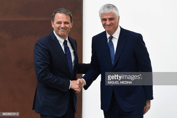 Deputy General Director of the LVMH group Antonio Belloni shakes hands with CEO of Thelios industry Giovanni Zoppas during the inauguration of the...