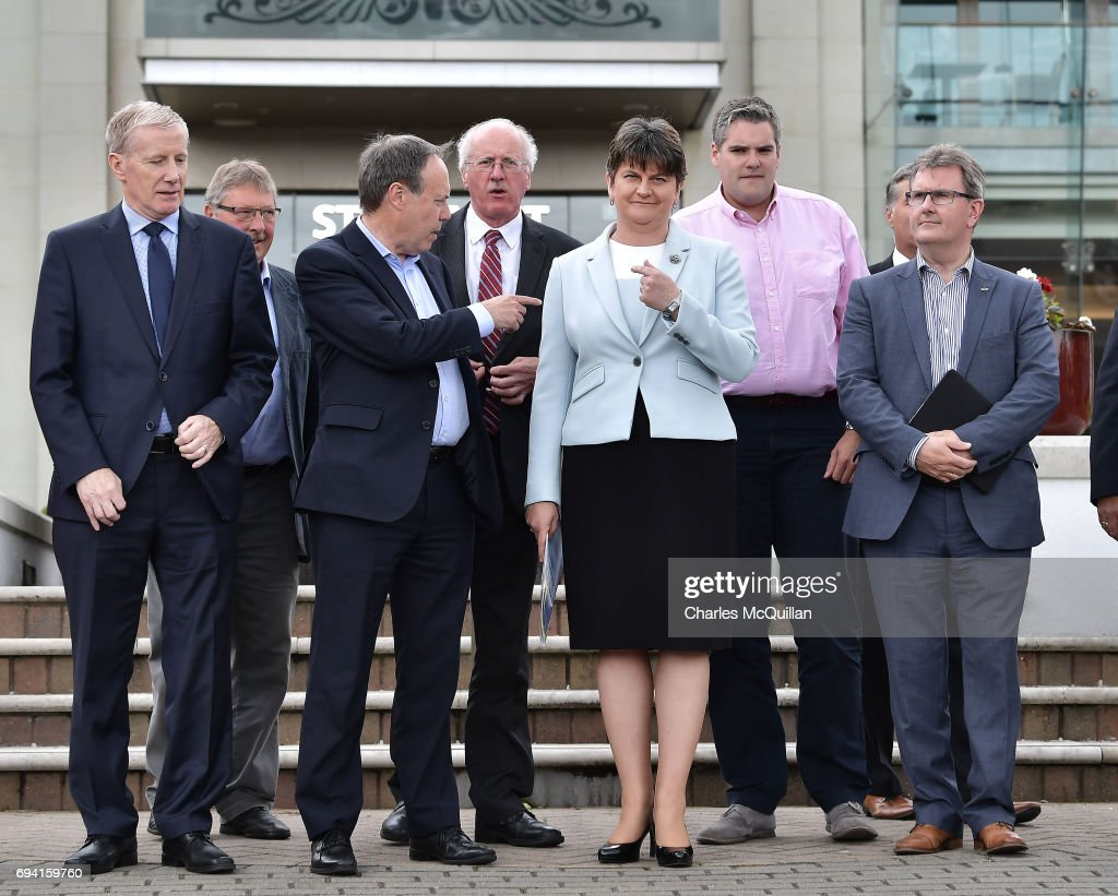 DUP deputy leader Nigel Dodds (L) points to DUP leader and Northern Ireland former First Minister Arlene Foster (R) as they hold a photocall with their newly elected candidates who stood in the general election on June 9, 2017 in Belfast, Northern Ireland. After a snap election was called by Prime Minister Theresa May the United Kingdom went to the polls yesterday. The closely fought election has failed to return a clear overall majority winner and a hung parliament has been declared. Arlene Foster and the Democratic Unionist party with their ten Westminster seats have today stated that they will back Theresa May and the Conservatives in a prop up goverment. The two parties will continue talks about the finer details of the arrangement.