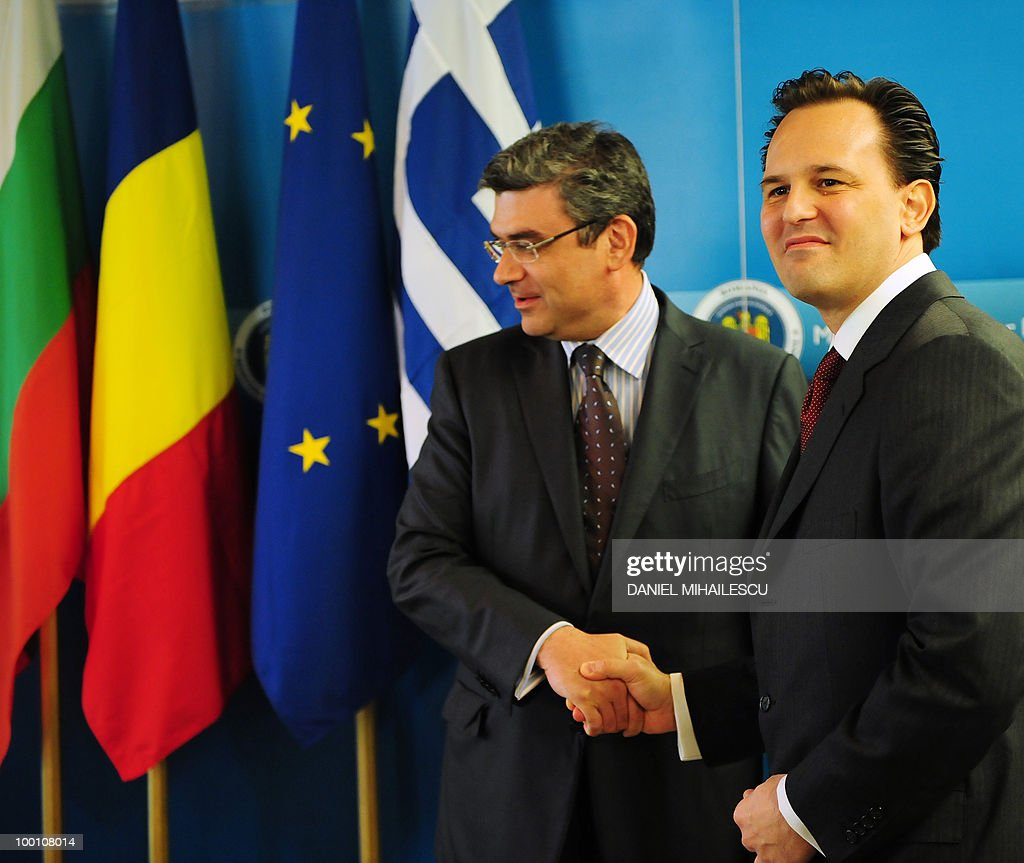 Deputy Minister of Greek Foreign Affairs Dimitris Droutsas (R) shakes hands with Romanian Foreign Minister Teodor Baconschi in Bucharest on May 21, 2010 at the beginning of the seventh tri-lateral Foreign Ministers meeting between Romania, Greece, and Bulgaria.
