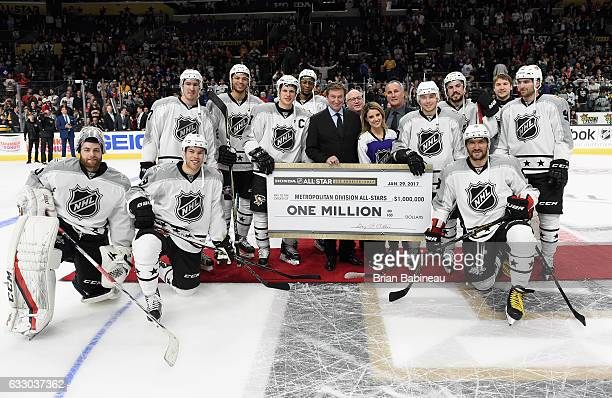 Deputy NHL Commissioner Bill Daly and anthem singer Courtney Daniels present the one million dollar winner's check to members of the Metropolital...