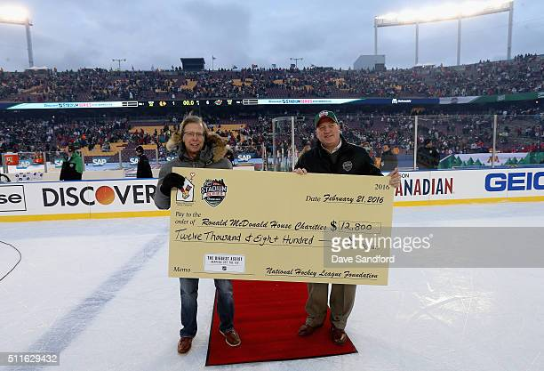 Deputy NHL Commissioner Bill Daly presents a $12800 check to Ronald McDonald House Charities after the 2016 Coors Light Stadium Series game between...