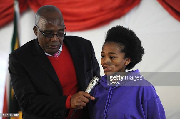 Deputy President Cyril Ramaphosa holds a microphone for Mpho Bagaqane during his visit at Nkosis Haven on July 13 2016 in Johannesburg South Africa...
