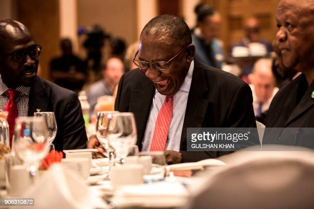 Deputy President of South Africa and newly elected African National Congress President Cyril Ramaphosa reacts while flanked by Minister of Finance...