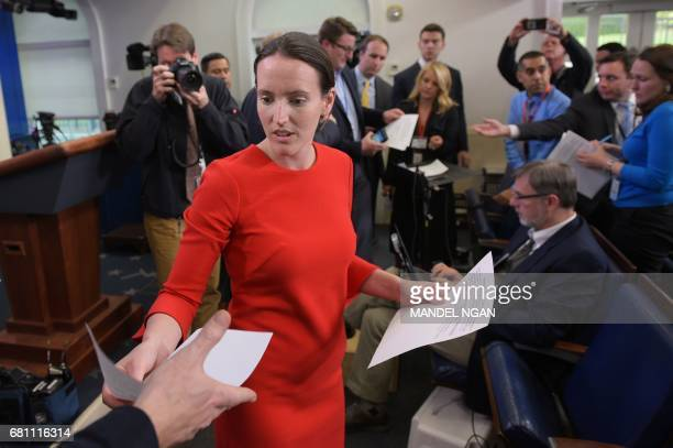 Deputy Press Secretary Lyndsey Walters hands out documents to reporters in the Brady Briefing Room of the White House advising them that there will...