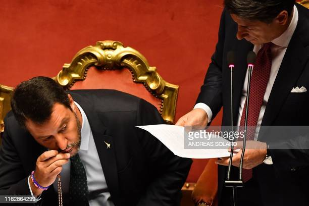 TOPSHOT Deputy Prime Minister and Interior Minister Matteo Salvini kisses a rosary as Italian Prime Minister Giuseppe Conte delivers a speech at the...