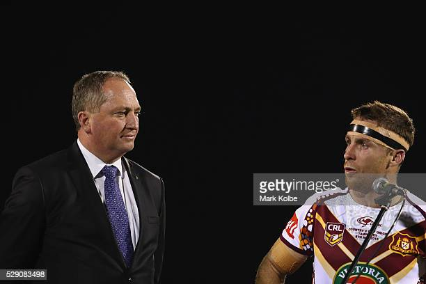 Deputy prime minister Barnaby Joyce watches on as James Maloney of Country speaks during the presentation ceremony after the NSW Origin match between...