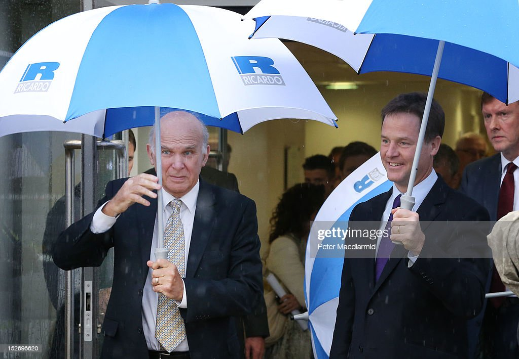 Deputy Prime Minister Nick Clegg (R) and Business Secretary Vince Cable shelter under umbrellas as they leave the Ricardo Engine Assembly plant on September 24, 2012 in Shoreham-by-Sea, England. Later the Business Secretary Vince Cable will announce a new bank to enable easier lending to businesses.