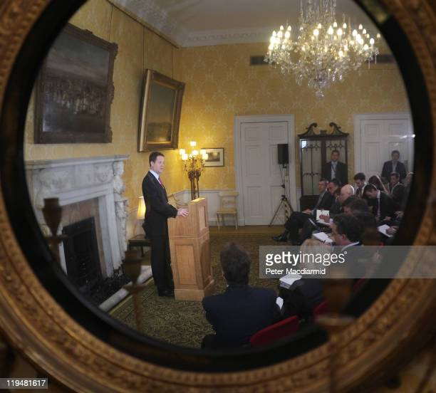 Deputy Prime Minister Nick Clegg image is reflected in a convex ornate mirror as he speaks to reporters at Admiralty House on July 20 2011 in London...