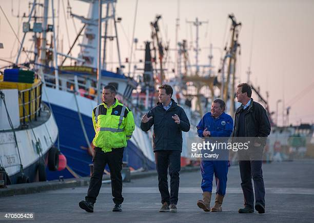 Deputy Prime Minister Nick Clegg walks past fishing vessels as he visits Newlyn Harbour accompanied by Harbour Master Rob Parsons and market manager...